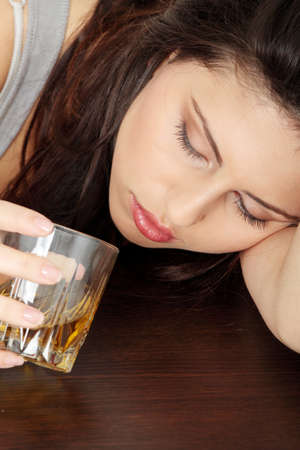 alcoholic drinks: Yound beautiful woman in depression, drinking alcohol