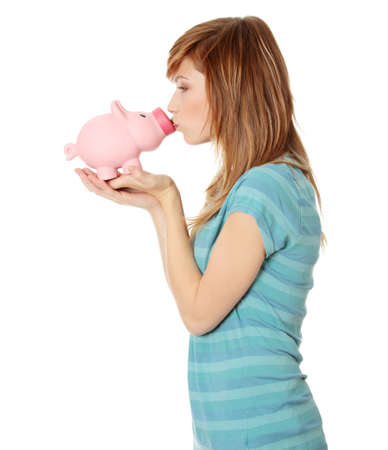 Young teen woman kissing a piggy bank, isolated on white  photo
