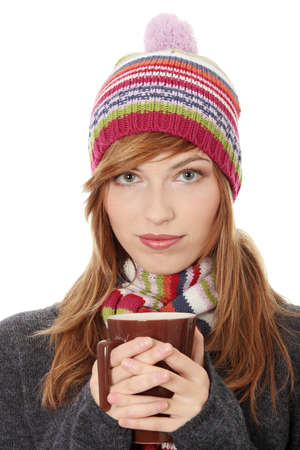 Young woman with winter cap drinking something hot, isoalted on white photo