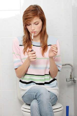 Teen girl smoking in bathroom photo