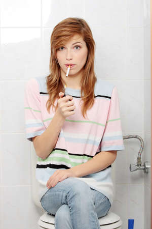 Teen girl caught on smoking in bathroom Stock Photo - 8830782