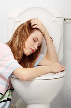 Young teen woman vomiting in toilet photo