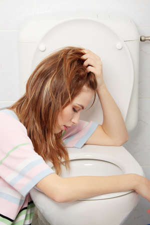 vomito: Joven adolescente v�mito en el inodoro Foto de archivo