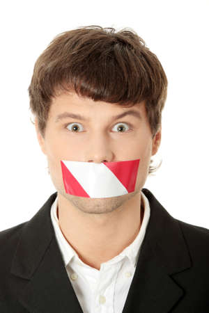 Freedom of speech concept. Young handsome businessman with red and white tape on his mouth. Isolated on white  photo