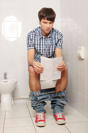 public toilet: Young handsome man sitting on toilet and reading magazine.