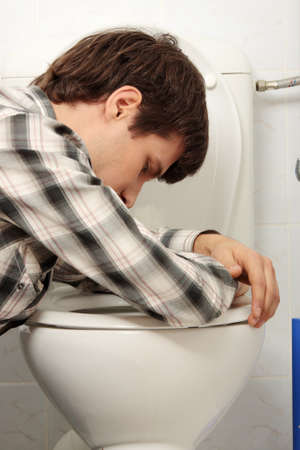 Young man (drunk or sick) vomiting photo