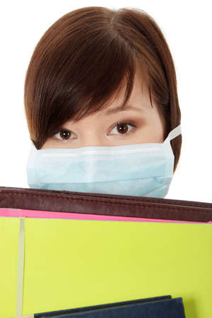 Close up portrait of young  student woman with mask on her face. She is defending her self from viruses. Isolated on white Stock Photo - 8830544