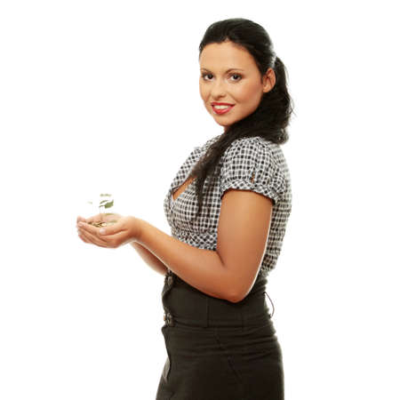 Young business woman holding small tree growing from coins. Isolated on white background photo