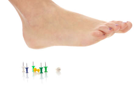 Female foot above pushpin, isolated on white background Stock Photo