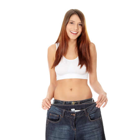 Woman showing how much weight she lost. Isolated  Stock Photo - 8828332