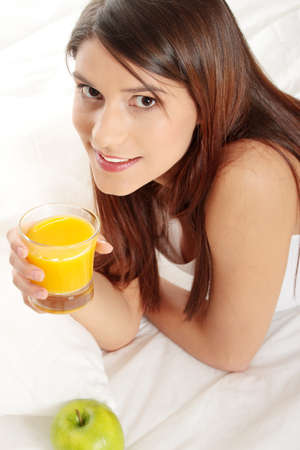 Young happy beautiful woman on bed holding orange juice photo