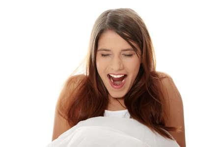 yawing: Hermosa joven mujer cauc�sica feliz en la cama, aislado en blanco