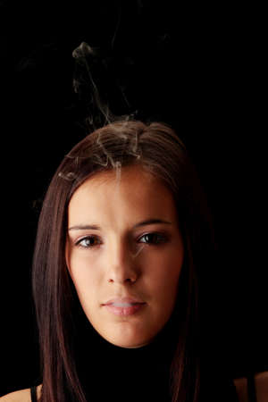Young woman smoking over black background photo