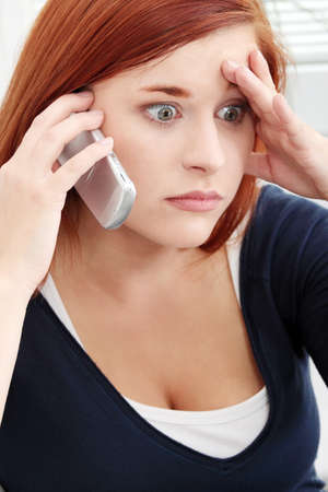 Young woman getting bad news by phone. photo