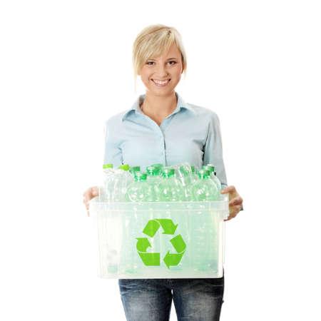 reciclable: Joven mujer llevando un recipiente de pl�stico lleno de vac�o dom�sticos reciclables. Concepto de reciclaje