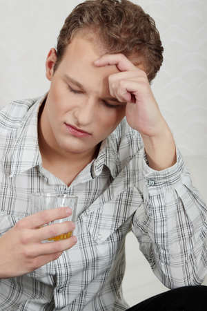 Attractive young guy drinking whiskey - depressed photo