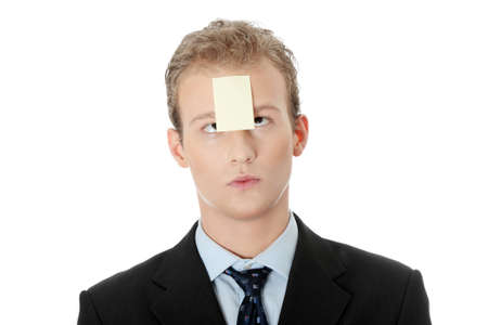 Businessman with memo stick message notes on forehead, over white studio background  photo