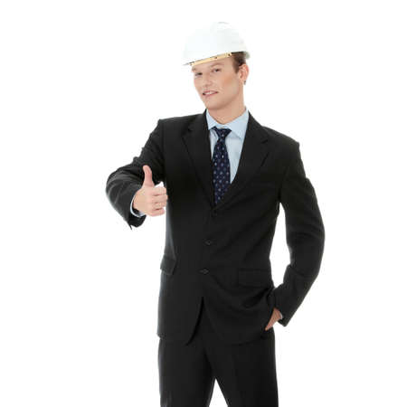Young businessman in white helmet gesturing ok, isolated on white photo