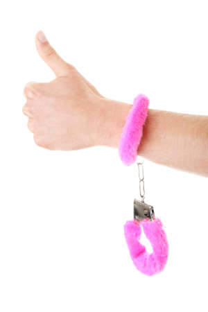 Young caucasian man hand with pink handcuff  photo
