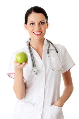Healthy eating or lifestyle concept. Smiling woman doctor with a green apple. Zdjęcie Seryjne
