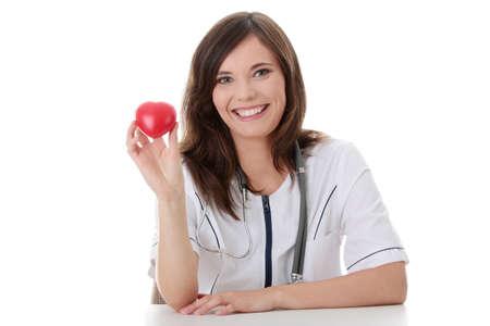 Giovane medico femmina con il cuore in mano.  Isolated on white Archivio Fotografico - 8957376
