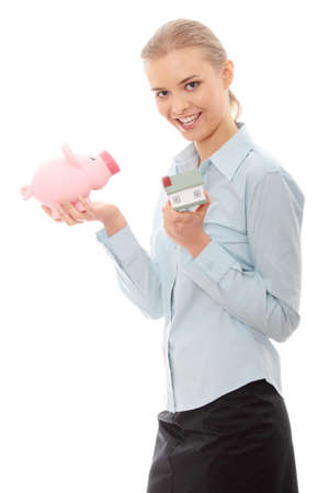 Young beautiful business woman with house model and piggy bank in hands, isolated on white background photo
