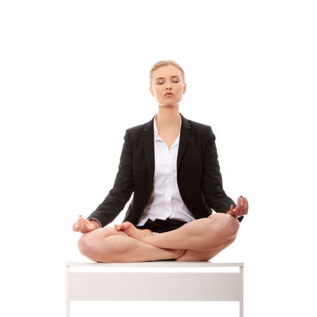 Beautiful blond businesswoman sitting on white desk in lotus flower position of yoga. Isolated on white photo