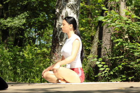 Young girl in lotus pose in the park  Stock Photo - 9021147