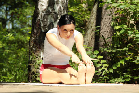 An attractive caucasian woman practicing yoga outdoors  Stock Photo - 9021584