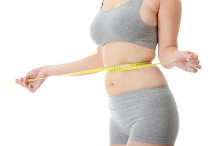 Frau messen ihre Taille, isoliert auf weiss