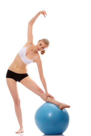 Young woman exercising with fitness ball. Isolated on white  photo