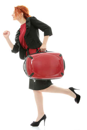 Young redhead businesswoman (deaf with hearing aid) with red suitcase, isolated on white background photo