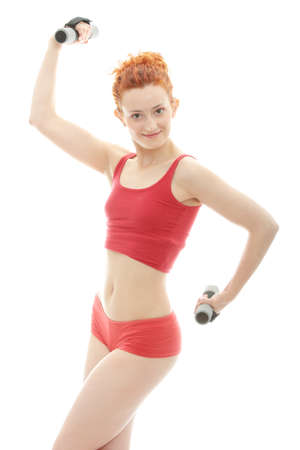 Beautiful, young, deaf (with hearing aid in ears) redhead exercising with dumb bells photo