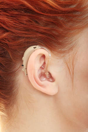 deafness: Redhead woman wearing hearing aid