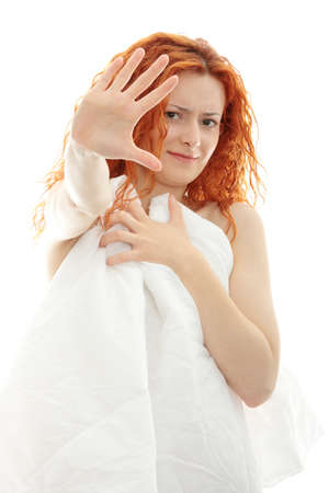 Shocked redhead woman covering her self with bedding photo