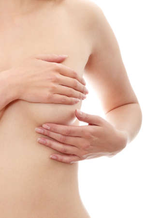 naked breast: Young Caucasian adult woman examining her breast for lumps or signs of breast cancer