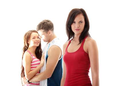 celos: La chica de celos contra la joven pareja, aislado en blanco  Foto de archivo
