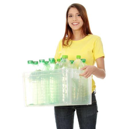 recyclage plastique: Jeune femme portant un contenant en plastique plein de plastique recyclable vide. Concept de recyclage.