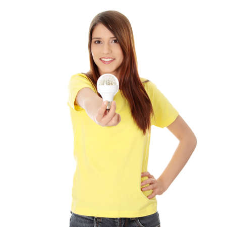 source of light: Young happy woman holding diode bulb, isolated on white  Stock Photo
