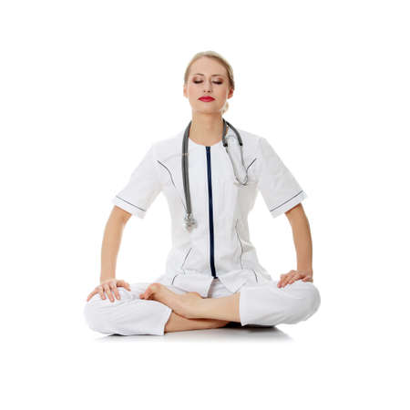 Young doctor or nurse doing yoga  Isolated on white  版權商用圖片