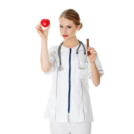 Young doctor or nurse holding heart  Isolated on white  photo
