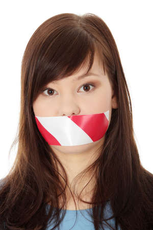 Freedom of speech concept. Young beautiful woman with red and white tape on her mouth. Isolated on white  photo