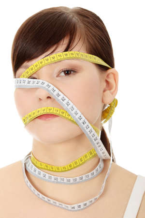 Young woman with measuring tape around her head, isolated on white. Diet concept  photo