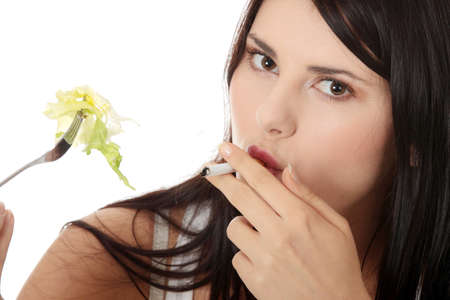 Girl eating salad and smoking sigarette. Unhealthy life concept Stock Photo - 9021303