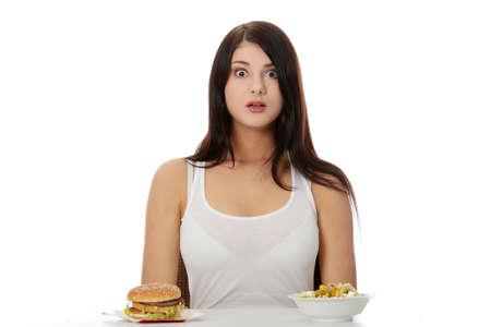 Beautiful caucasian woman thinking whot to eat: hamburger or salat. Isolated on white photo