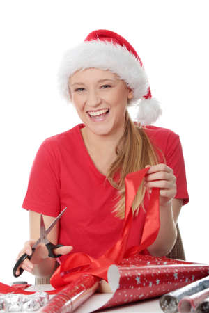 Young blond woman in santa hat packing christmass gift photo