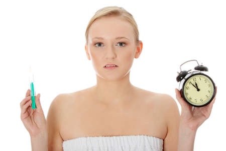 Young woman with syringe and clock, isolated photo
