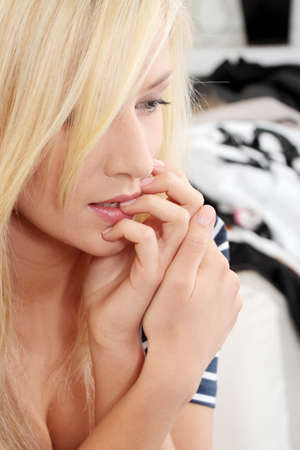 Stressed young woman eating her nails Stock Photo - 9021491
