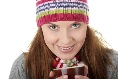 Young woman in cap drinking something hot, isolated on white photo