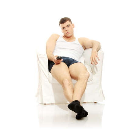 Young man in underwear, sitting in armchair with remote control in hand - bored. Isolated on white photo